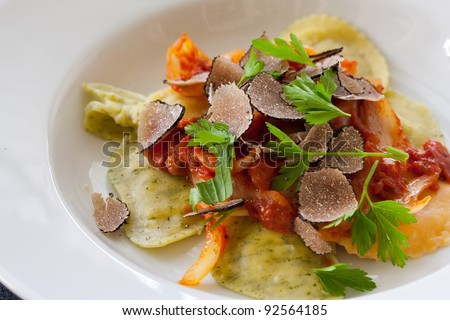 Freshly made italian ravioli pasta with slices of black truffle - stock photo