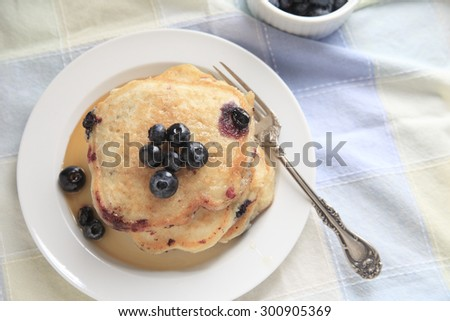 Freshly made pancakes with blueberries and syrup on a plate with fork, copy space included - stock photo