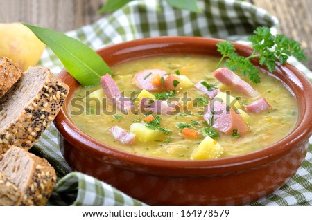 Freshly made potato soup with bacon strips and Vienna sausage wheels - stock photo