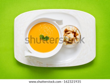 Freshly made pumpkin soup served on green with croutons - stock photo