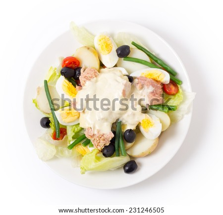 Freshly made traditional nicoise salad with tuna, boiled egg, potato, mayo, beans, olives and lettuce. - stock photo