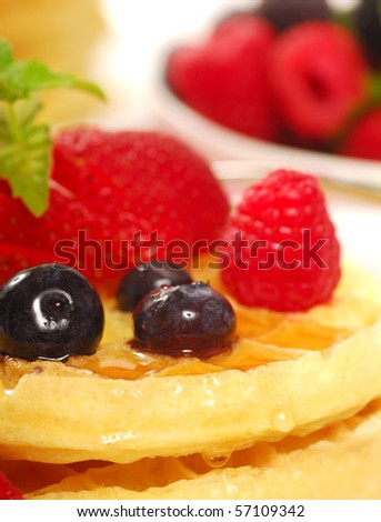 Freshly made waffles with a variety of fruit and maple syrup - stock photo