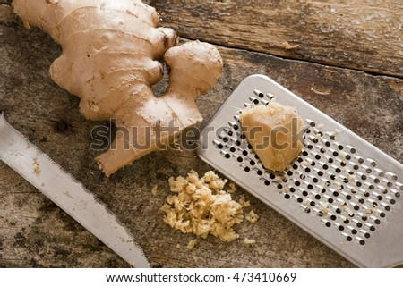 Freshly minced or grated root ginger on an old wooden kitchen table with a portion of whole root and a stainless steel grater or rasp