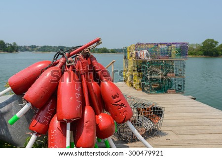 Freshly painted red lobster boats and colorful yellow lobster traps sit on a working pier dock as they await loading onto outbound lobster boats - stock photo