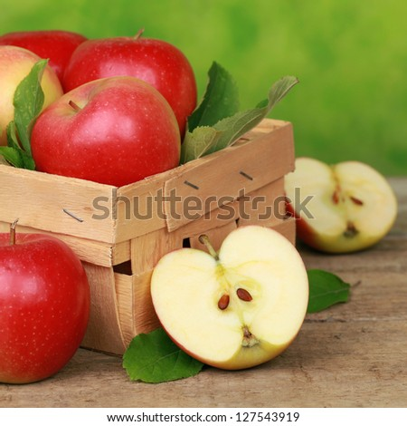 Freshly picked apples with leaves in a wooden box