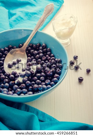 Freshly picked blueberries in a blue bowl with cream. Blueberries with yogurt. Juicy and fresh Bilberry on white table. Healthy breakfast. Concept for healthy eating and nutrition. Selective focus. - stock photo