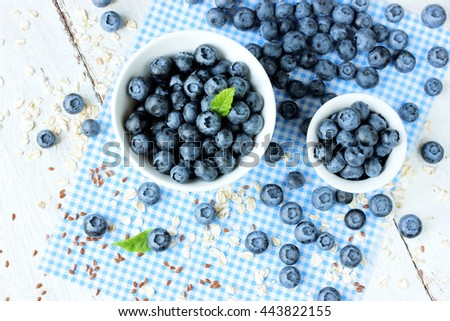 Freshly picked blueberries in white bowl. Juicy and fresh blueberries. Bilberry on wooden background. Blueberry antioxidant. Concept for healthy eating and nutrition - stock photo