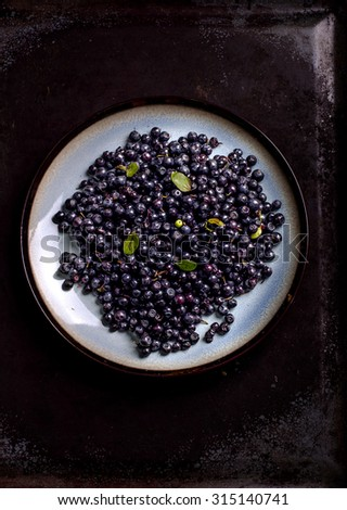 freshly picked blueberries on the plate against a dark background - stock photo