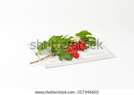 freshly picked branch of red currant with green leaves, on the wooden cutting board - stock photo
