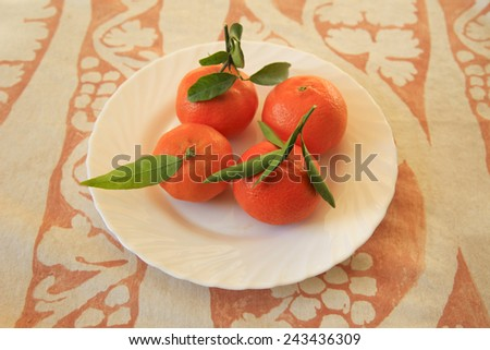 Freshly picked oranges on a plate - stock photo