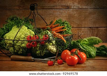 Freshly picked vegetables on metal basket in wooden table - stock photo