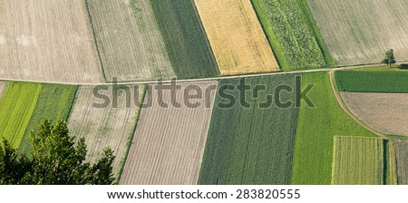 Freshly plowed and sowed farming land from above, neatly cultivated in non-urban agricultural area, textured effect and background. Food production industry, arable land concept. - stock photo