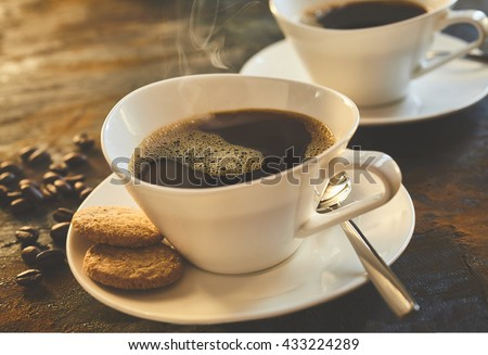 Freshly poured cup of espresso coffee served with cookies in an elegant modern white cup and saucer with scattered coffee beans alongside - stock photo