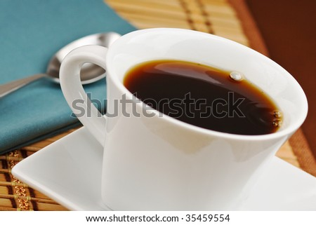 Freshly poured cup of hot black coffee - stock photo