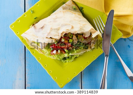 Freshly prepared and colorful  crepe with vegetables and chicken on green plate and blue wood table - stock photo