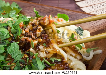 Freshly prepared Asian noodles on a brown wooden plate. - stock photo