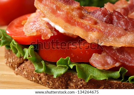 Freshly prepared bacon, lettuce, and tomato sandwich on whole grain wheat toast.  Macro with extremely shallow dof. - stock photo