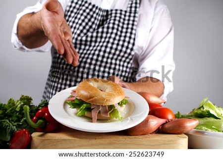 freshly prepared bagel served by chef - stock photo
