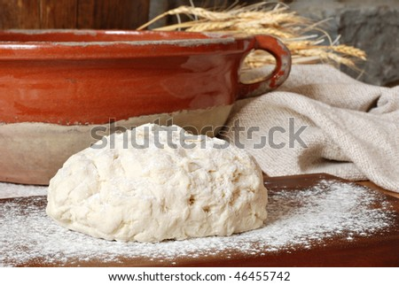 Freshly prepared bread dough with rustic bowl, homespun fabric and wheat spikes against stone background.  Close-up with shallow dof. - stock photo