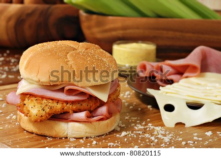 Freshly prepared chicken cordon bleu sandwich on wood cutting board with breadcrumbs.  Swiss cheese, ham, honey mustard, and celery in soft focus in background.  Macro with shallow dof. - stock photo