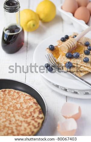 Freshly prepared crepes with maple syrup & blueberries - shallow dof - stock photo