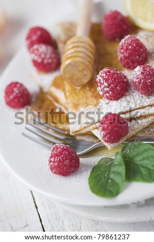Freshly prepared crepes with raspberries - shallow dof - stock photo