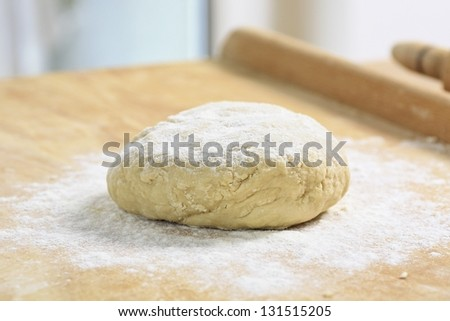 Freshly prepared dough lying on wooden table