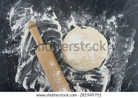 Freshly prepared dough on a wooden board. Rolling pin and flour on table. Top view. - stock photo