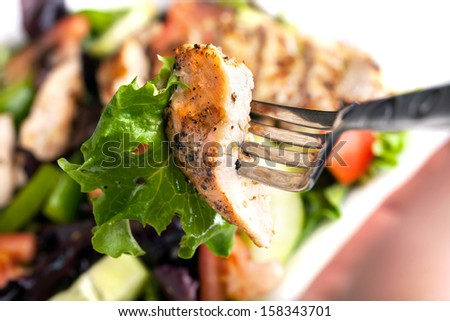 Freshly prepared grilled chicken chef style salad with tomato cucumber green pepper and romaine lettuce. - stock photo