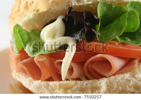 Freshly prepared ham and salad roll with mayo.