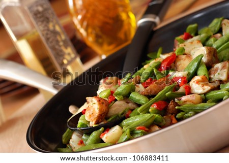 Freshly prepared mixed vegetables with gourmet herb sauce in eco friendly ceramic coated skillet.  Closeup with shallow dof.  Selective focus on veggies in spoon. - stock photo