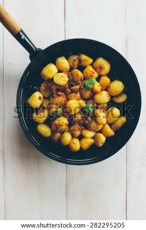 Freshly prepared organic potatoes in a pan on a vintage wooden table. Retro styled imagery, grain added - stock photo