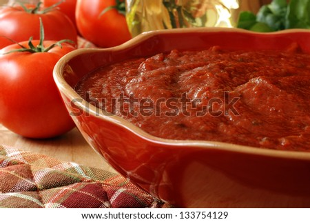 Freshly prepared pasta or pizza sauce in decorative bowl with tomatoes, olive oil, and herbs in background. Closeup with shallow dof.