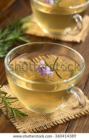 Freshly prepared rosemary herbal tea in glass cups, garnished with rosemary flowers, photographed on dark wood with natural light (Selective Focus, Focus on the first flowers) - stock photo