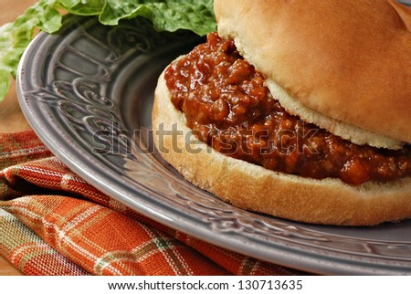 Freshly prepared sloppy joe sandwich on decorative plate with romaine lettuce.  Macro with shallow dof. - stock photo