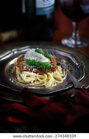 Freshly prepared Spaghetti Bolognese from an authentic Italian recipe with grated parmesan cheese and basil garnish. The perfect image for an Italian restaurant menu cover design. - stock photo