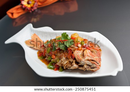Freshly prepared Thai style whole fish red snapper dinner with tamarind sauce on a white fish shaped plate. Shallow depth of field. - stock photo