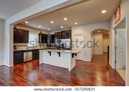 Freshly remodeled kitchen room interior. Furnished with dark wood cabinets and large kitchen island in the middle. Northwest, USA