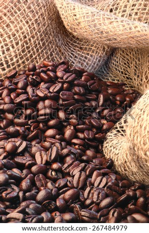 Freshly roasted coffee beans with a burlap background - stock photo