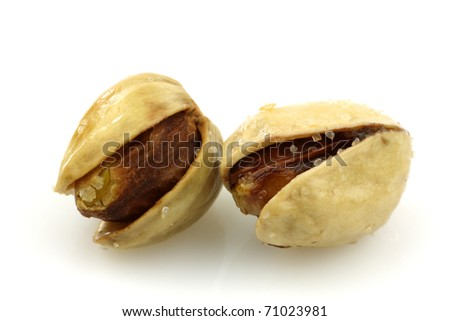 freshly roasted pistachio nuts on a white background - stock photo