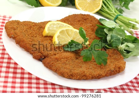 freshly roasted wiener schnitzel with lemon slices and parsley - stock photo