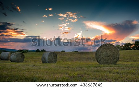 Freshly rolled bales of hay are seen on a rolling hill during a magnificent sunset - stock photo