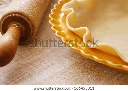 Freshly rolled pie crust (in dish ready to be fluted and filled) with flour dusted vintage rolling pin on wood background.  Macro with shallow dof and copy space. - stock photo