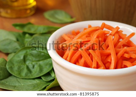 Freshly shredded carrots in small dish with baby spinach and salad oil in soft focus in background.  Macro with extremely shallow dof. - stock photo