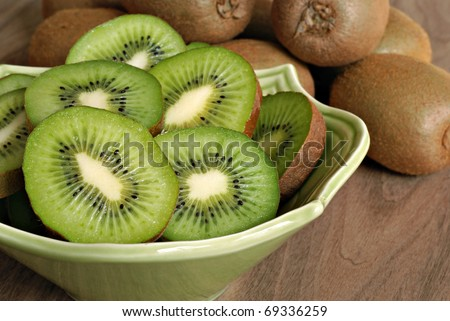 Freshly sliced kiwi fruit with whole kiwis in background.  Closeup  with shallow dof. - stock photo