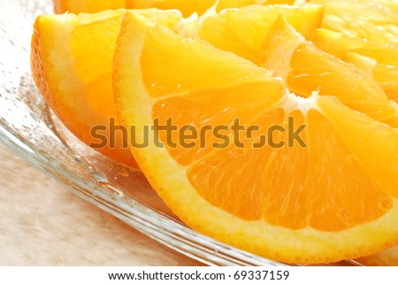 Freshly sliced oranges on glass plate.  Macro with shallow dof. - stock photo