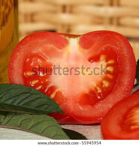 Freshly sliced tomato with mint leaves and olive oil - stock photo
