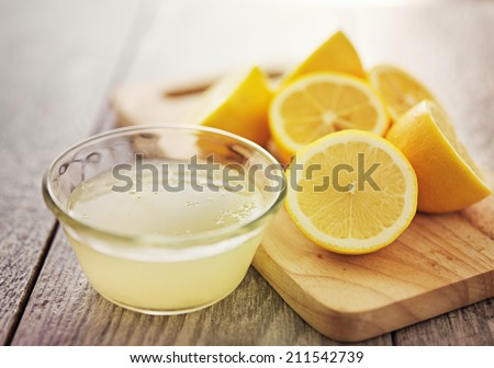 freshly squeezed lemon juice in small bowl - stock photo