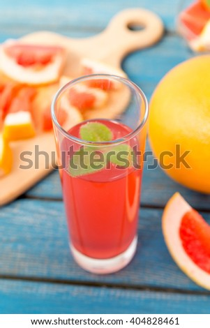 Freshly squeezed orange and grapefruit juice in glass, with fruits on wooden background