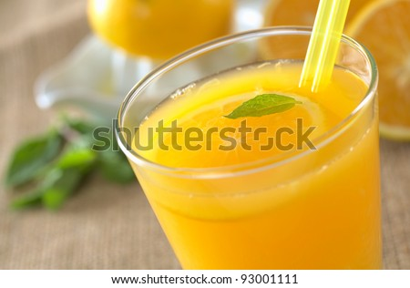 Freshly squeezed orange juice with drinking straws and orange slice, mint leaf on top of the juice (Selective Focus, Focus on the mint leaf in the glass)